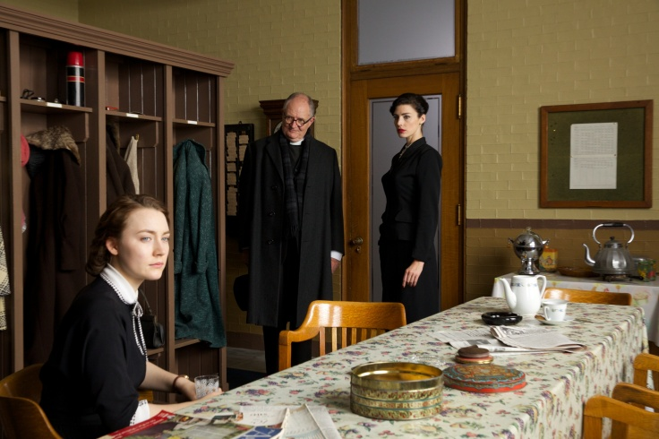 Saoirse Ronan as Eilis, Jim Broadbent as Father Flood and Jessica Paré Miss Fortini